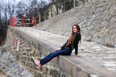 Brunette girl wearing leather jacket, blue jeans and pink sneakers royalty free stock images