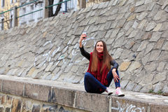 Brunette girl wearing leather jacket, blue jeans and pink sneakers. Beautiful teenager in casual fashion taking a picture with her smart phone royalty free stock image