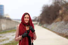 Brunette girl wearing leather jacket with a red scarf. Beautiful smiling teenager in casual fashion standing on the street in winter time royalty free stock images