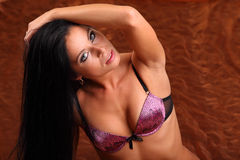 Brunette girl wearing pink bra looks mysteriously Royalty Free Stock Images