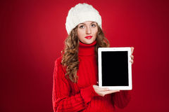 Brunette girl wearing red sweater and holding tablet Stock Images