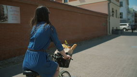 Brunette girl wearing sunglasses cycling near buildings. Cars parked near the road, slow mo, steadicam shot stock video