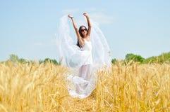 Brunette girl wearing white dress standing in Stock Images