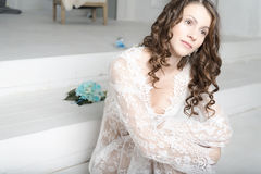 Brunette girl in white dress sitting on the stairs. Royalty Free Stock Images