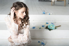 Brunette girl in white dress sitting on the stairs. Stock Photo