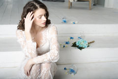 Brunette girl in white dress sitting on the stairs. Royalty Free Stock Image