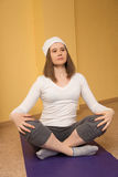 Brunette girl in white practicing yoga in the lotus position royalty free stock photography