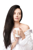 Brunette girl in white shirt holding cup with hot beverage and looking away Stock Photography