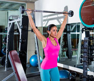 Brunette girl wide grip barbell shoulder press gym Royalty Free Stock Photo