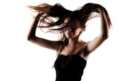 Beautiful brunette girl with windy hair. Brunette girl with windy hair posing against white background Royalty Free Stock Image