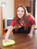Brunette girl wiping the dust from wooden furniture Royalty Free Stock Images