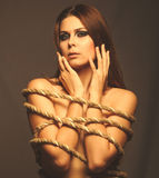 Brunette girl woman bound with rope prisoner in jeans gray backg Stock Photography