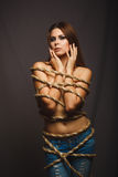 Brunette girl woman bound with rope prisoner Stock Image