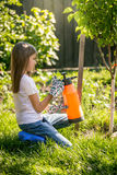 Brunette girl working in garden with fertilizing spray Royalty Free Stock Photography