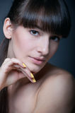 Brunette girl with yellow nail polish Stock Photos