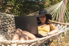 Brunette girl in a yellow swimsuit sitting in a hammock using a laptop, work on vacation, freelance, remote work, online earnings.  royalty free stock image