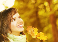 Brunette with golden autumn leaf Stock Photography