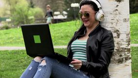 Brunette on the grass with a computer. Brunette in nature with a computer with headphones listening to music stock footage