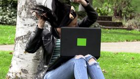 Brunette on the grass with a computer. Brunette in nature with a computer with headphones listening to music stock video