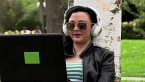 Brunette on the grass with a computer. Brunette in nature with a computer with headphones listening to music stock video footage