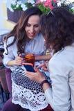 Brunette graziose che praticano il surfing su Internet in smartphone sopra la tazza della t Fotografia Stock