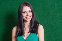 Brunette in green dress against wall Royalty Free Stock Photos