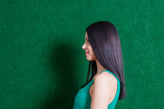 Brunette in green dress against wall Royalty Free Stock Photography