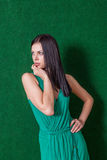 Brunette in green dress against wall Stock Photography