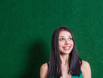Brunette in green dress against wall Royalty Free Stock Images
