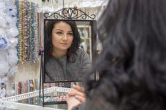 Brunette with green eyes admires herself in the mirror stock photos