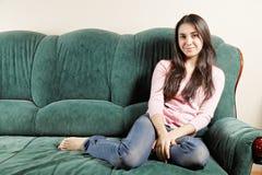 Brunette on green sofa Royalty Free Stock Photos