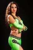 Brunette in a green suit oriental dance Stock Image