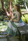 Brunette in green white dress on a bench. A beautiful young woman with long brown hair in a green-white dress sitting on a bench in a park in summer stock image