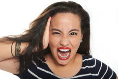 Brunette gril screaming. Brunette girl angry with freckles screaming on white background Stock Images