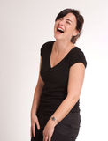 Brunette guffawing. Portrait of a laughing attractive green eyed  brunette  dressed in black Royalty Free Stock Images