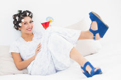 Brunette in hair curlers and wedge shoes holding a cocktail Stock Photo