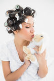 Brunette in hair rollers kissing sheep teddy Royalty Free Stock Image