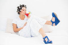 Brunette in hair rollers and wedge shoes drinking a cocktail Royalty Free Stock Photo