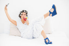 Brunette in hair rollers and wedge shoes drinking a cocktail taking a selfi Stock Photo