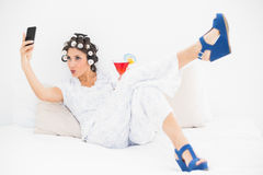 Brunette in hair rollers and wedge shoes having a cocktail takin Stock Photos