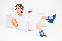 Brunette in hair rollers and wedge shoes holding a cocktail gest Stock Images