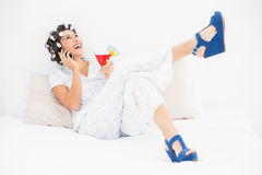 Brunette in hair rollers and wedge shoes holding a cocktail maki Stock Photo