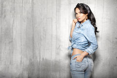 Brunette hair woman in jeans. Beautiful brunette hair woman in jeans in loft background Stock Image