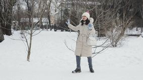 Brunette hair young women with pink lips in beige down coat and hat funny dancing snowy central park, snowfall. Slow stock video footage