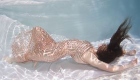 Woman wearing a gown holding her breathe underwater. Stock Image