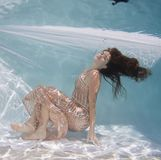 Woman wearing a gown holding her breathe underwater. Royalty Free Stock Images