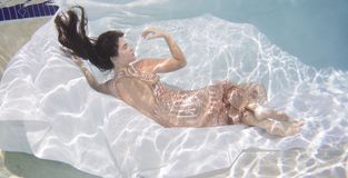 Woman wearing a gown holding her breathe underwater. Stock Images