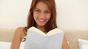 Brunette haired woman reading a novel. On her bed stock footage