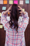 Brunette with hands on hair in front of sticky notes on wooden wall Royalty Free Stock Photo