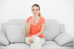 Brunette happy woman holding a glass of water smiling at camera Stock Photos